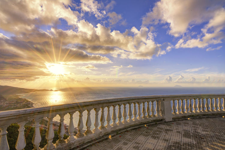 Observation point by sea against sky during sunset