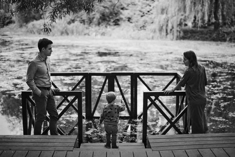 Happy family in the spring park stands on the bridge by the river Adult Blackandwhite Boys Casual Clothing Child Childhood Daughter Family Family Time Females Full Length Girls Group Of People Leisure Activity Lifestyles Males  Men Nature Outdoors Parent Positive Emotion Son Standing Togetherness Women