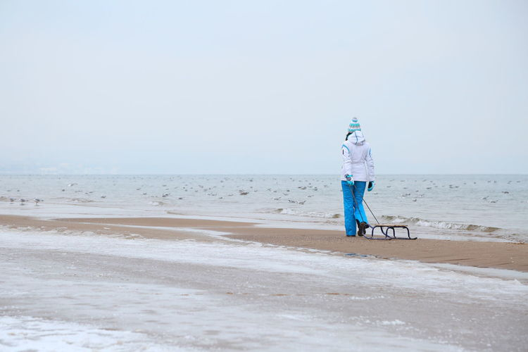 Adult Baltic Sea Beach Beauty In Nature Cold Day Full Length Horizon Over Water Nature One Person Outdoors People Sand Sea Sea And Sky Sky Sled Sledge Sleigh Vacations Walking Wave Winter EyeEmNewHere Long Goodbye Live For The Story