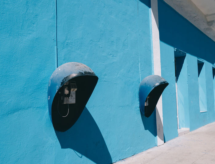 Close-up of blue container on wall