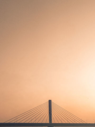 Low angle view of suspension bridge against sky during sunset