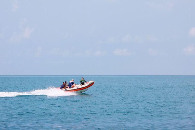 People On Motorboat In Sea Against Sky