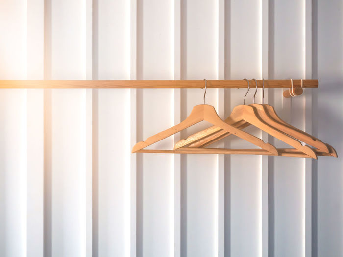 Wooden hangers for hanging clothes with wood clothes rack on white stripe wall.