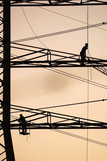 Sky Cable Electricity  Occupation Power Supply Working Men Low Angle View Fuel And Power Generation Real People Power Line  Silhouette Technology Connection RISK Outdoors Clear Sky