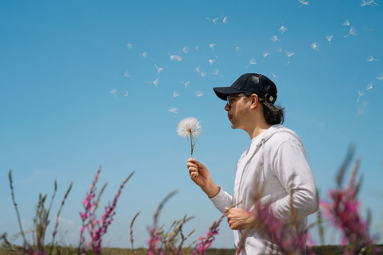 Woman standing by dandelion against sky