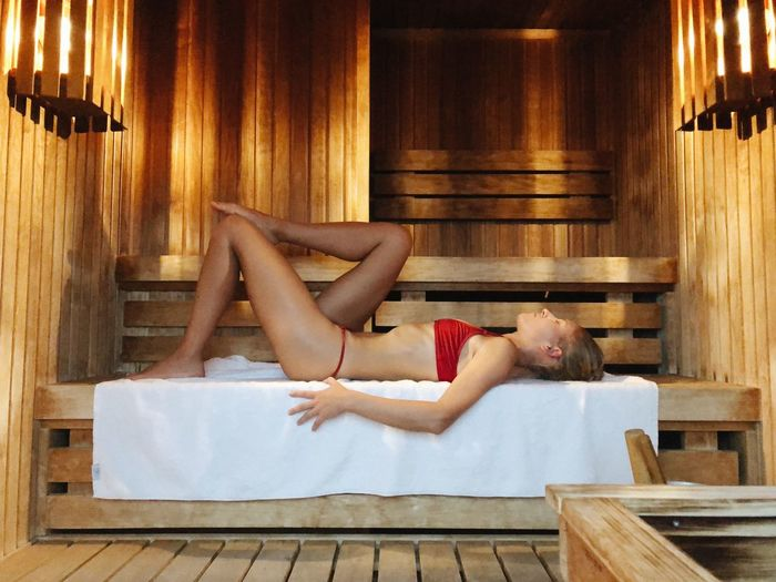 Side view of young woman relaxing in the sauna