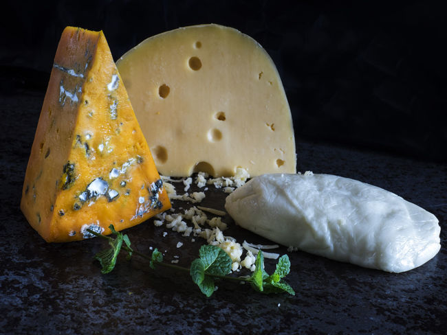 Fresh pieces of cheese (Mozzarella, roquefort, Maasdam) on the stone table Background Black Cheese France Fresh Italy Maasdam Mint Mozzarella Netherlands No People Pieces Roquefort Slate Switzerland Table
