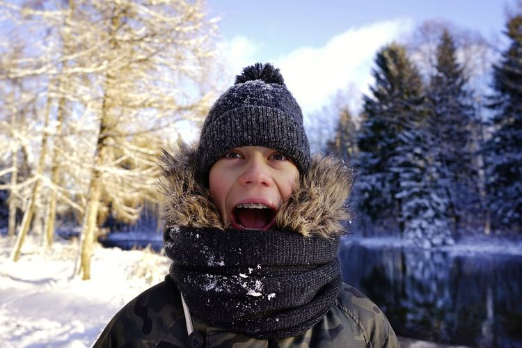 Portrait Of Teenage Boy Wearing Warm Clothing While Screaming Against Lake During Winter