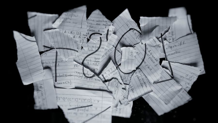 High angle view of torn papers on black background