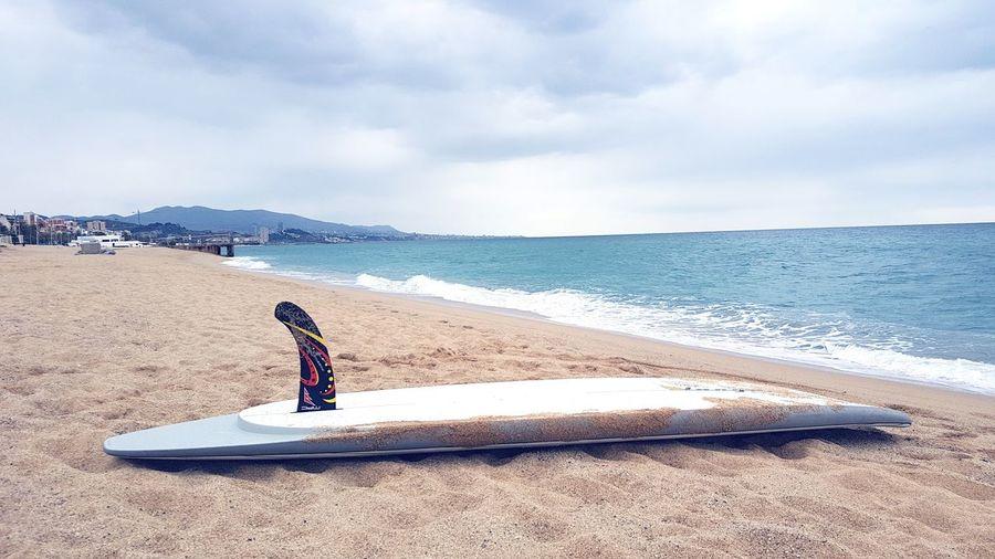 Surfboard on sandy beach against cloudy sky