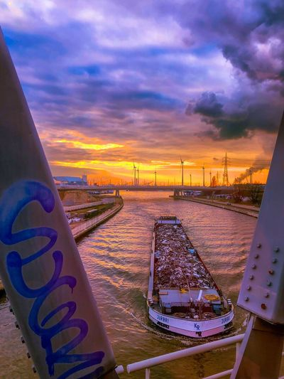Large river transport boat going underneath a bridge over the river scheldt at sunset showing the Golden glow in the sky under the dark and blue sky above Cloud - Sky Sky Sunset Communication Text Nature Western Script No People Land Outdoors Sign Transportation Beauty In Nature Mode Of Transportation Scenics - Nature Water Railing Tranquility Purple