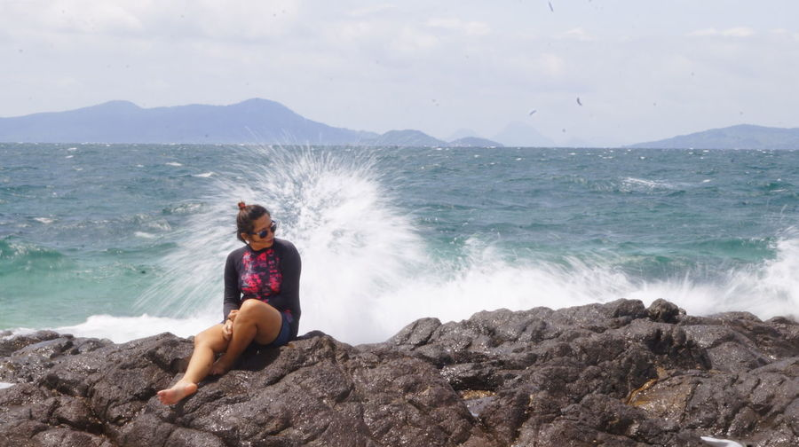 Full length of young woman on rock at beach against sky