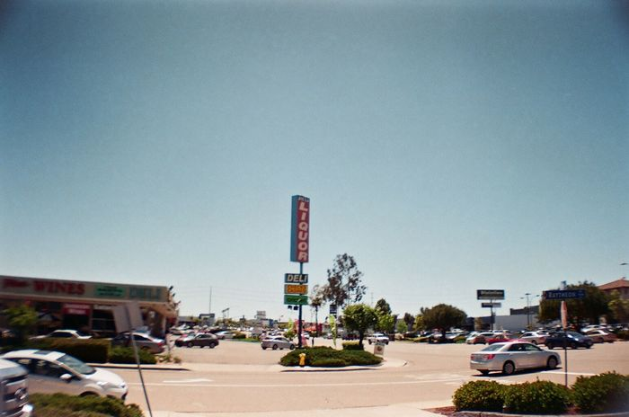 suburbia 35mm Film Agfa Vista200 Americana Analogue Photography California Clear Sky Convenient Store Cornershop Daytime Filmisnotdead Liquor Store Lomography Mode Of Transport On The Road Parking Lot Retro Sign Road Trip San Diego Socal Vibe Street Intersection Strip Mall Suburban Landscape Suburbia Vignette