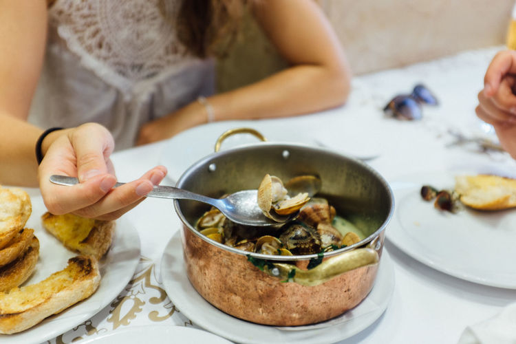 Midsection of woman eating seafood at table