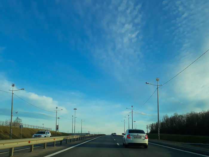 Cars on road against blue sky