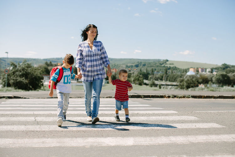 Full length of mother and children on zebra crossing