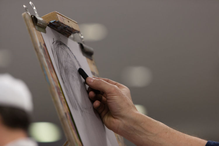 Cropped hand of person drawing on artist canvas
