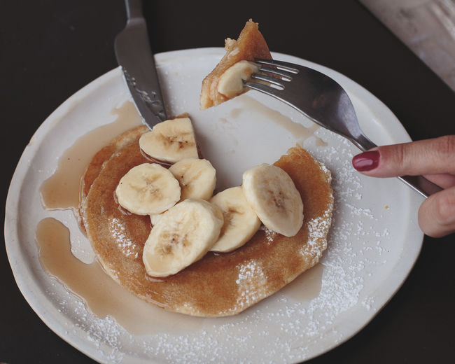 Banana Body Part Breakfast Eating Utensil Finger Food Food And Drink Fork Freshness Hand Healthy Eating Holding Human Body Part Human Hand Indoors  Indulgence Kitchen Utensil One Person Pancakes Plate Ready-to-eat Real People Snack Temptation Unrecognizable Person