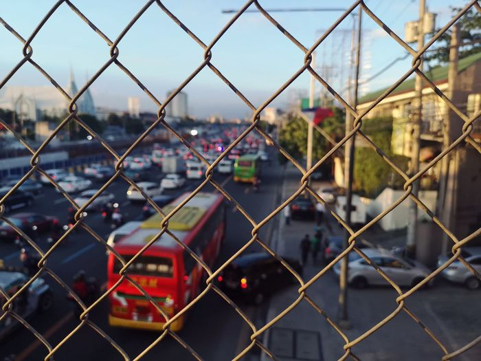 Close-up of chainlink fence against cityscape