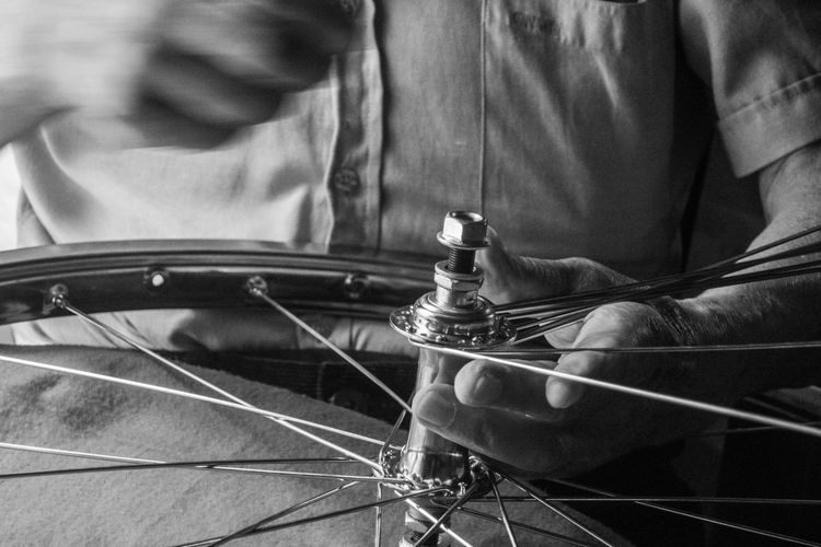 Midsection Of Mechanic Repairing Bicycle Wheel At Workshop