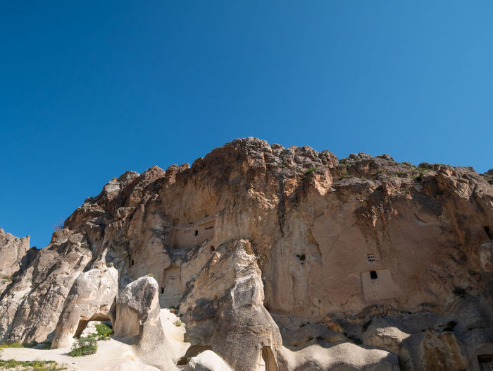 Low angle view of rocks against clear blue sky