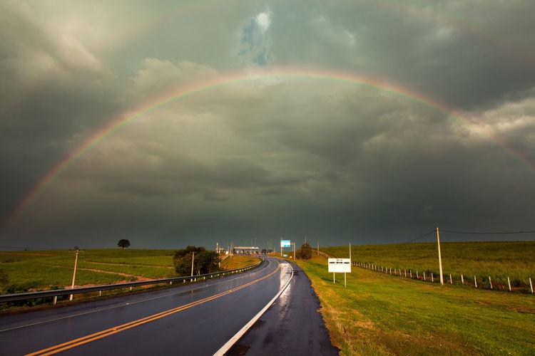 Rainbow over road against cloudy sky