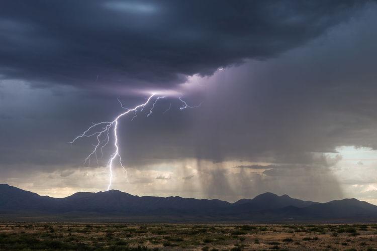 Lightning over landscape against cloudy sky