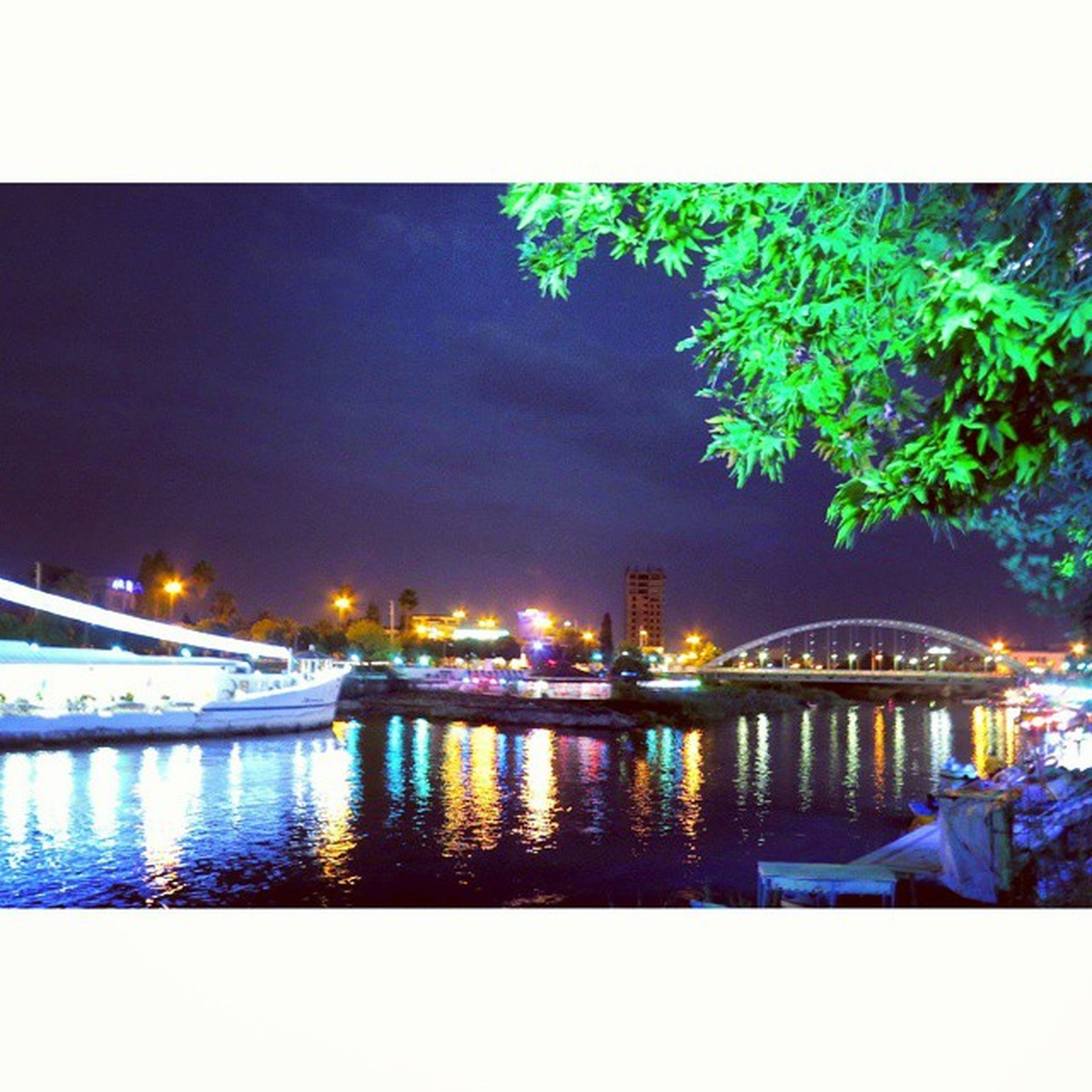 illuminated, water, night, reflection, architecture, built structure, building exterior, river, transfer print, city, waterfront, auto post production filter, nautical vessel, transportation, sky, lake, lighting equipment, boat, bridge - man made structure, moored