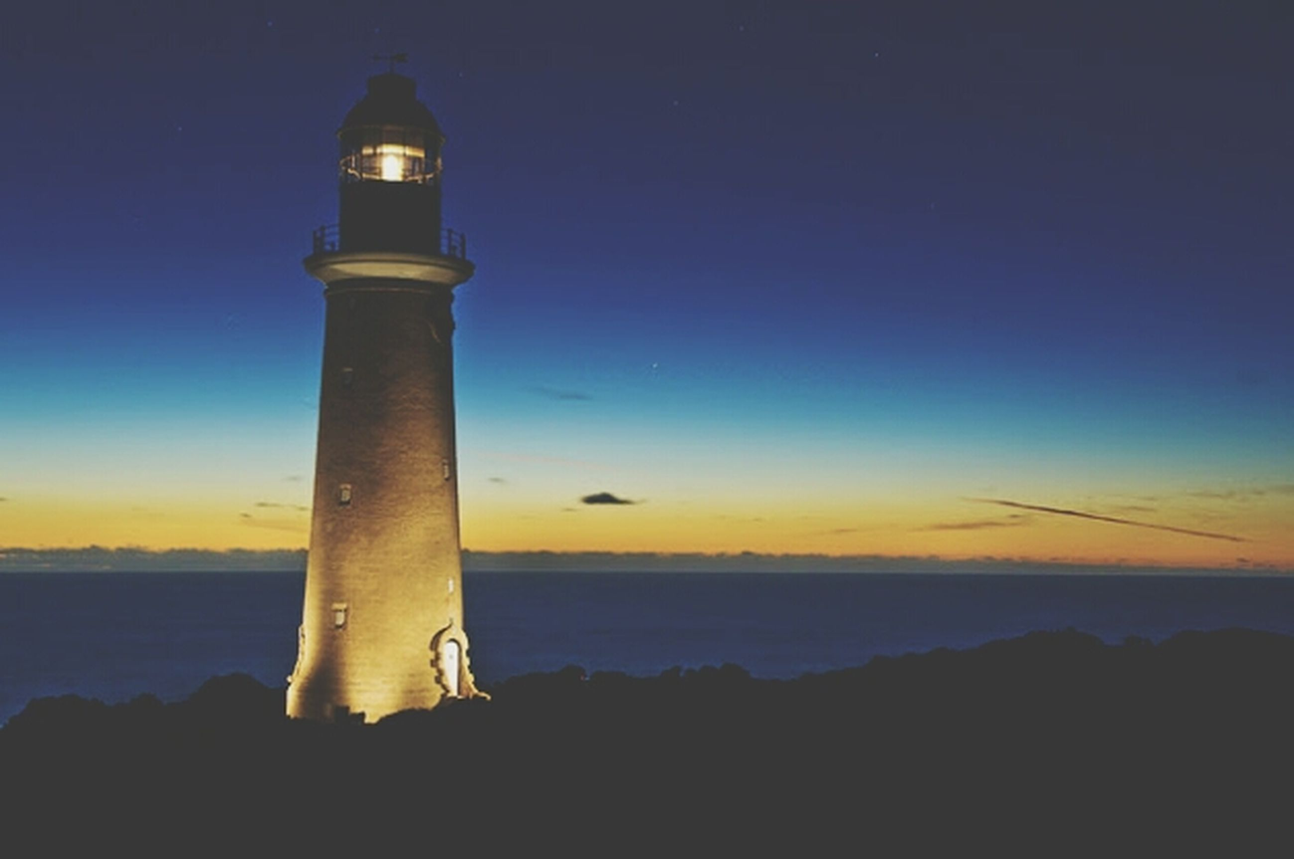 sea, lighthouse, water, horizon over water, sky, sunset, scenics, tranquil scene, tranquility, beauty in nature, silhouette, guidance, nature, protection, built structure, blue, idyllic, dusk, outdoors, copy space