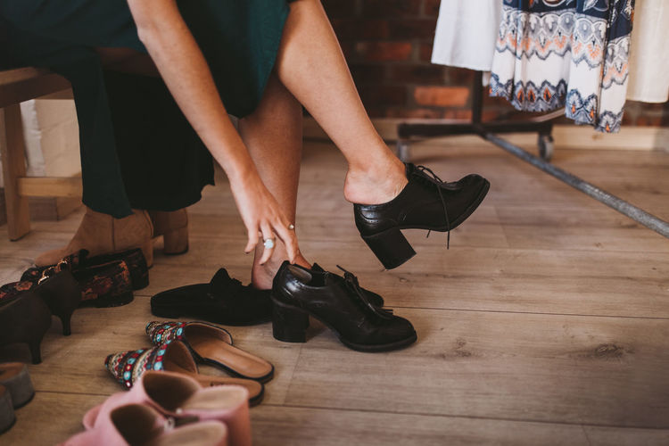 Low Section Real People Indoors  Women Shoe Adult One Person Body Part Lifestyles Leisure Activity Flooring High Heels Fashion Sitting Wood Holding Human Limb Shoe Shoes Getting Dressed