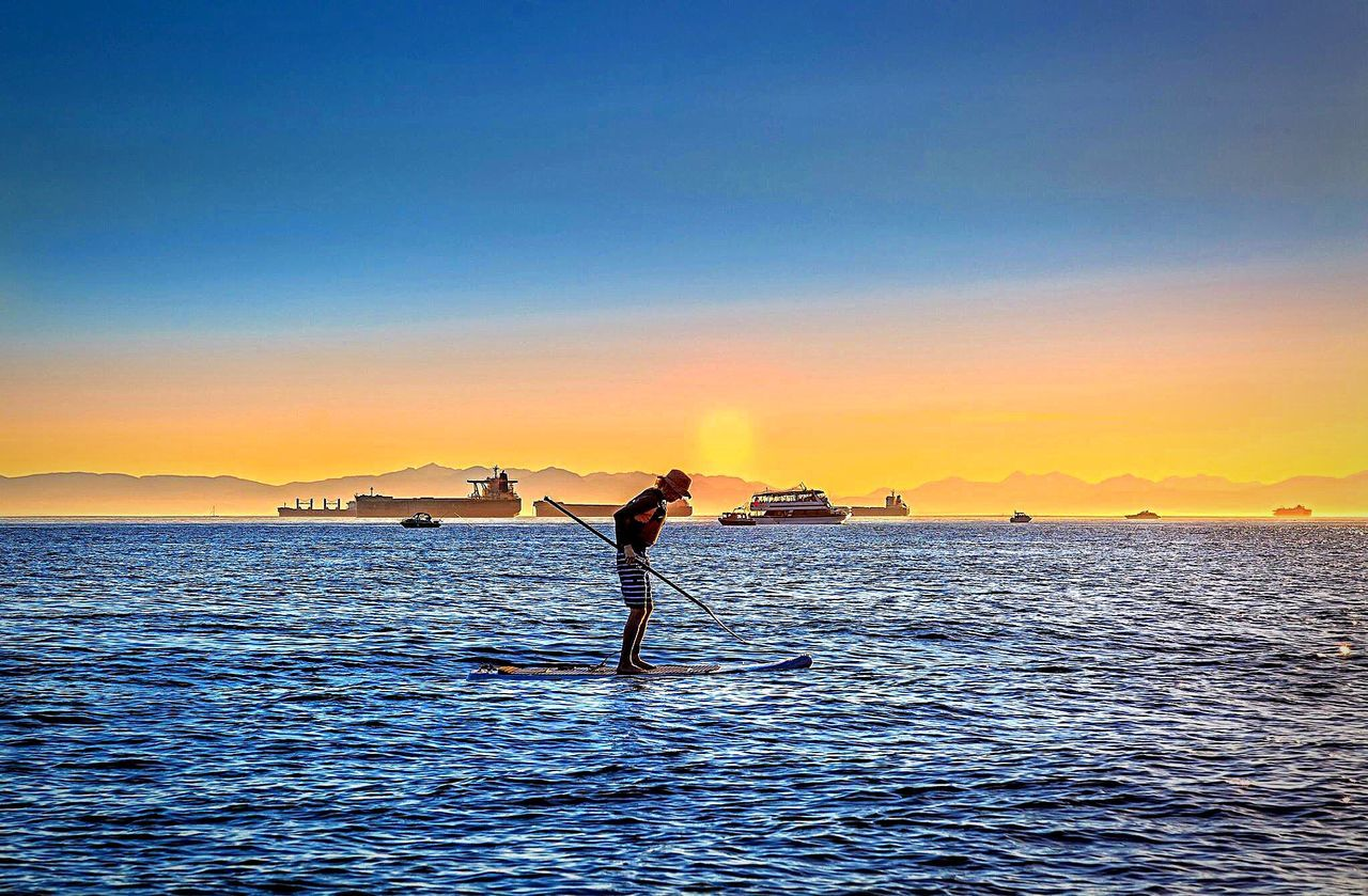 water, sea, real people, one person, sunset, beauty in nature, scenics, nature, outdoors, full length, balance, standing, tranquil scene, leisure activity, lifestyles, horizon over water, tranquility, sky, paddleboarding, clear sky, day, people