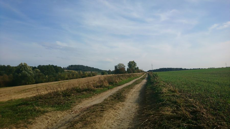 Dirt Road Passing Through Grassy Field Against Cloudy Sky