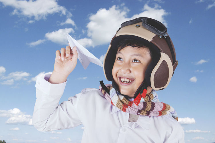Close-up of happy boy holding paper airplane while wearing helmet against cloudy sky