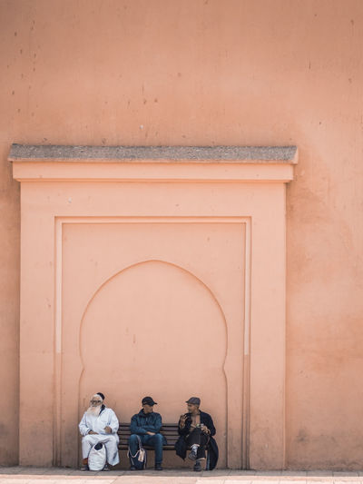 Rear view of men sitting on wall of building