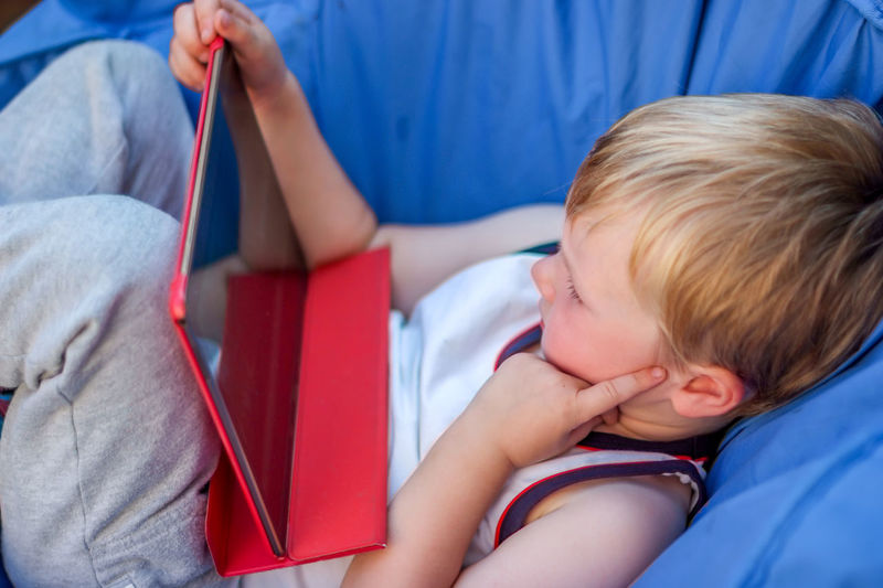 Little Blond Boy watching digital tablet with face expression Tablet Blond Blond Hair Childhood Close-up Day Device Screen Digital Expression Face Gadget Headshot Indoors  Real People Watching
