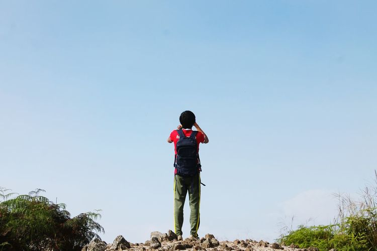 Rear view of man with backpack standing against clear sky