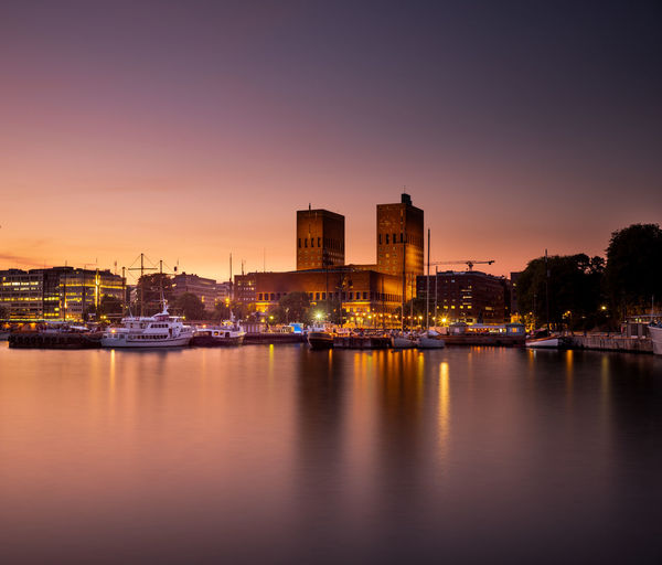 Oslo City Hall in the twilight. Building Exterior Water Architecture Reflection City Built Structure Illuminated Sunset No People Waterfront Cityscape Outdoors Oslo Oslo City Hall Twilight Evening Golden Hour Harbour Norway's Resistance Museum Summer Exploratorium colour of life EyeEmNewHere