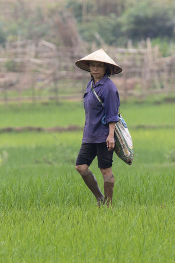Woman working a a rice paddyfield HUAWEI Photo Award: After Dark Casual Clothing Clothing Day Field Full Length Grass Green Color Growth Hat Land Landscape Leisure Activity Lifestyles Nature One Person Outdoors Plant Real People Standing Women