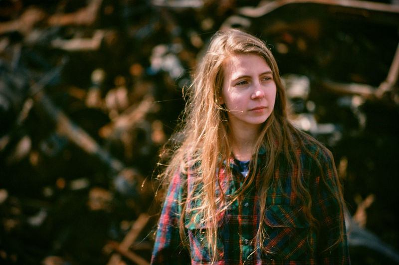 Young woman standing in front of crushed cars  in an auto salvage yard