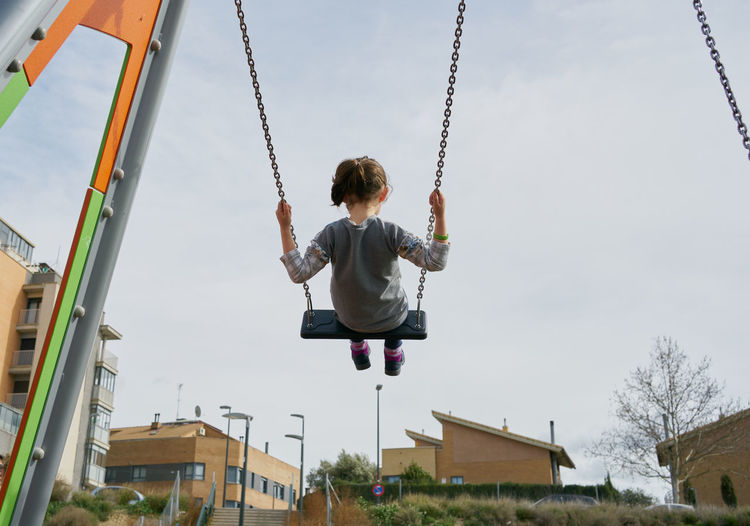 Low angle view of swing at playground against sky