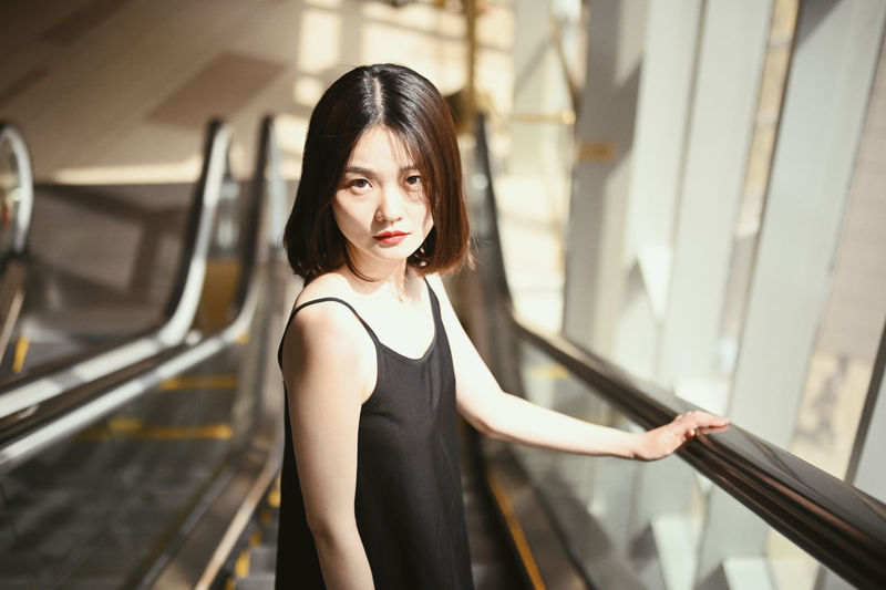 Portrait of woman standing on escalator