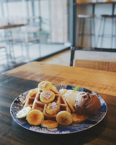 Close-up of waffles with banana and ice cream on table at cafe