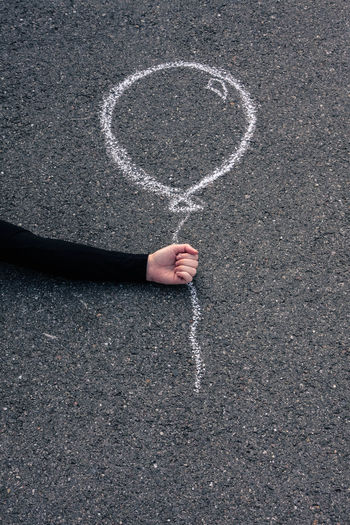 Optical illusion of hand holding balloon drawing on road