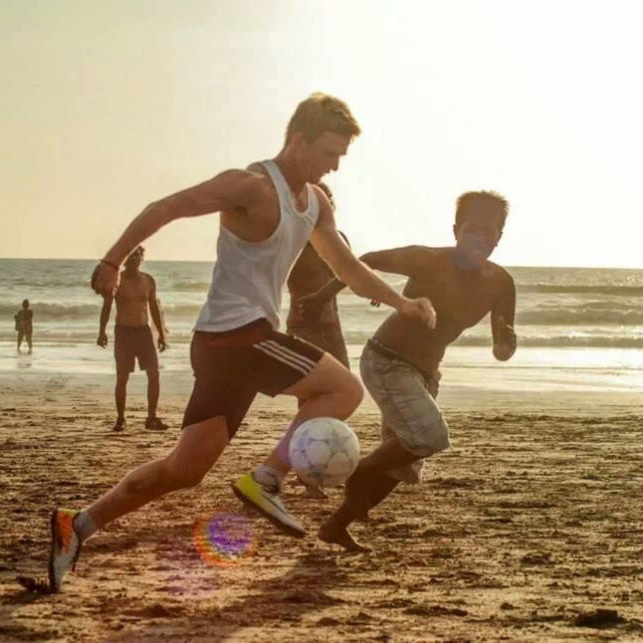 beach, playing, running, sand, soccer ball, soccer, motion, vitality, competition, sea, full length, sport, adult, people, outdoors, leisure activity, men, togetherness, group of people, boys, child, day, sunset, competitive sport, young adult, sports race, american football - ball, sportsman, sky