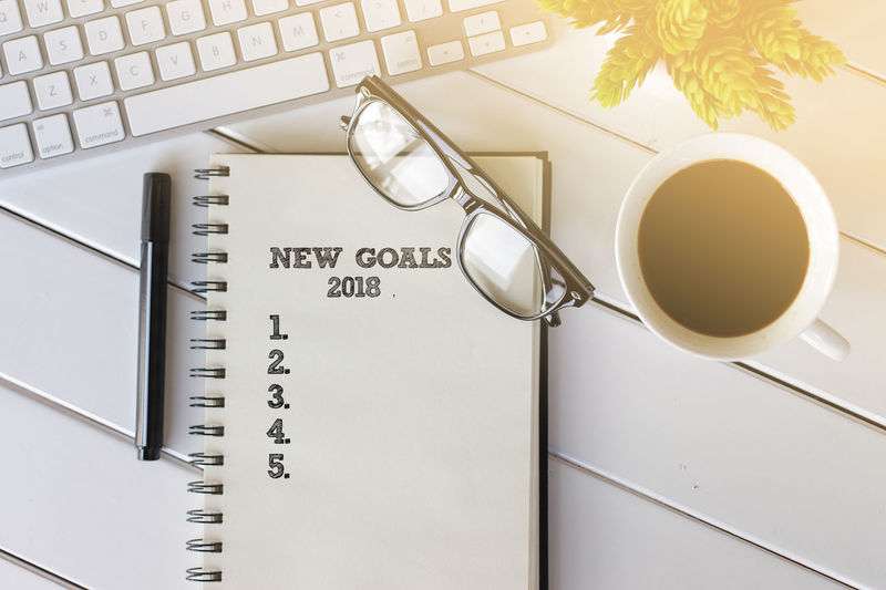 Top view notebook with keyboard and coffee cup writing new goals 2018 Business Achievement Check This Out Motivation New Purpose Career, Challenge Concept Goal Improvmment Job Notebook Notebook Paper Objective Occupation Optimization Potential  Profession Solution Strategy Success Vision
