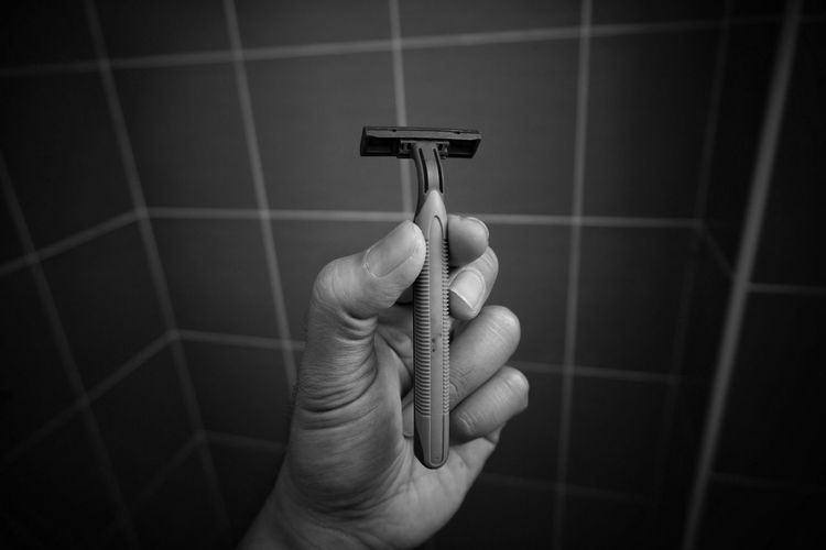 Cropped hand of man holding razor against wall