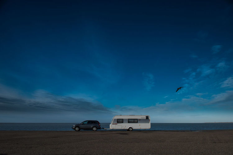 Camping Wohnwagen Beach Beauty In Nature Blue Caravan Cloud - Sky Day Horizon Over Water Nature No People Outdoors Sand Scenics Sea Sky Transportation Vacations Water