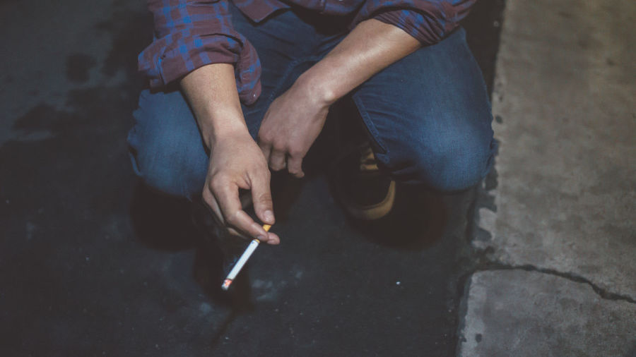 Low section of man smoking cigarette