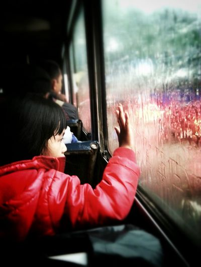 Rear view of woman touching condensed bus glass