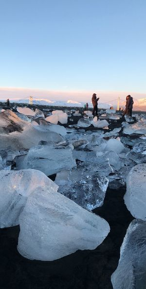 Tourist Enjoying Amidst Ice Cubes Against Sky During Sunset